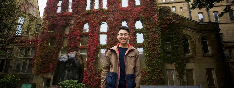 smiling person in front of vine covered wall
